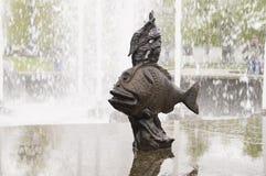 Fiska skulptur i brons på en marmortjock skivaspringbrunn Arkivbild