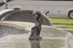 Fiska skulptur i brons på en marmortjock skivaspringbrunn Fotografering för Bildbyråer