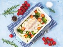 Fiska torsk som bakas i blå ugn med grönsaker - broccoli, tomater banta sund mat Bakgrund för blå sten, bästa sikt arkivfoton