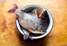Fiskar i maträtten eller bunken på tabellen i köket Arkivbild