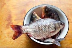 Fiskar i maträtten eller bunken på tabellen i köket Arkivbilder