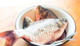 Fiskar i maträtten eller bunken på tabellen i köket Arkivfoton