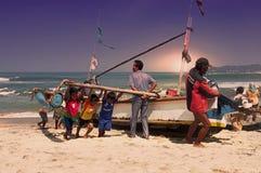 Fiskare, barn och traditionellt fartyg Arkivbild