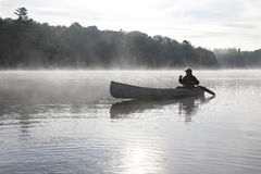 Fiskare Canoeing på en Misty Lake Royaltyfri Fotografi