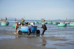 Fiskare drar det runda plast- fartyget från havet Fiskehamnen av Mui Ne, Vietnam Arkivbild