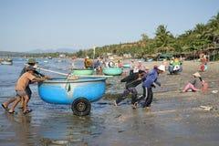 Fiskare drar ett plast- fartyg från havet Fiskehamnen av Mui Ne, Vietnam Arkivfoto