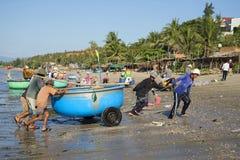 Fiskare efter det hav släpade runda plast- fartyget ashore Fiskehamnen av Mui Ne, Vietnam Arkivfoto
