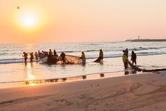 Fiskare förtjänar soluppgång för fartygstrandlansering Royaltyfri Fotografi