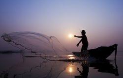 Fiskare fångar fisken med en ensemble netto. Fotografering för Bildbyråer