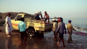 Fiskare från UAE släpar det netto med fisken i baksidan av bilen Al Akah Beach Fujairah arkivfilmer