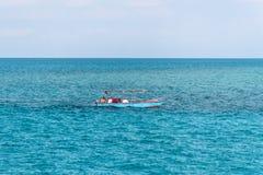 Fiskare går i havet för att fiska i litet fartyg Royaltyfri Foto