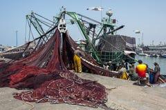 Fiskare går tillbaka med deras lås till den upptagna hamnen på Essaouira i Marocko royaltyfri bild