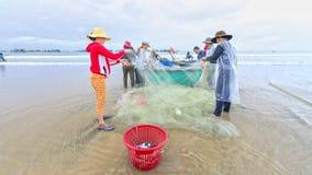 Fiskare gör illavarslande fisknät för arbete arkivbild