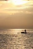 Fiskare i fartyget på soluppgång Arkivbild