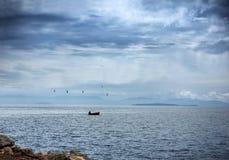 Fiskare i hans lilla fartyg under en dramatisk blå himmel arkivbild