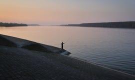 Fiskare i solnedgångögonblick på den Danube River sidan Royaltyfri Bild