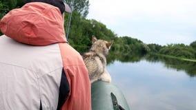 Fiskare med en hund i ett fartyg stock video