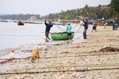 Fiskare med färgrika fiskebåtar på Februari 7, 2012 i Mui Ne, Vietnam Fotografering för Bildbyråer