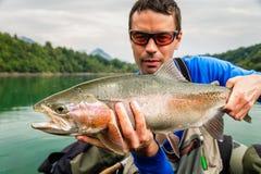 Fiskare med låset av regnbågeforellen, Slovenien Royaltyfri Foto