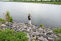 Fiskare med metspöet på flodbanken Arkivbilder