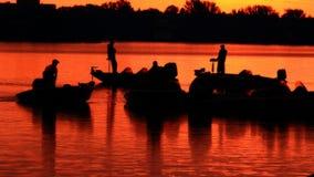 Fiskare och där fartyg för sport på soluppgången Arkivfoto