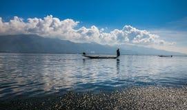 Fiskare och deras reflexion i vattnet Arkivfoton