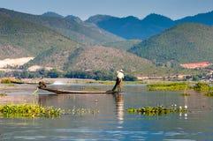 Fiskare och deras reflexion i vattnet Arkivbild