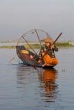Fiskare och hans reflexion på sjön Arkivbild
