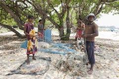 Fiskare och kvinnor som förbereder deras fisknät på delftfajansön i den nordliga regionen av Jaffna i Sri Lanka arkivfoton