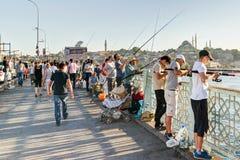 Fiskare och turister är på Galataen som bron kan på 26, 2013 Arkivbild