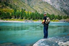 Fiskare p? bergfloden p? den trevliga sommardagen Forellflugafiske i bergfloden med berg i bakgrund royaltyfri fotografi