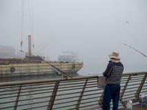 Fiskare på den industriella pir på dimmig dag royaltyfri bild