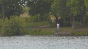 Fiskare på den motsatta kusten av sjön lager videofilmer