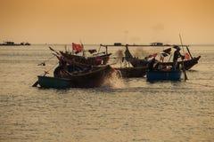 Fiskare på den runda och långa fartygflötet på havet mot solnedgång Arkivfoton