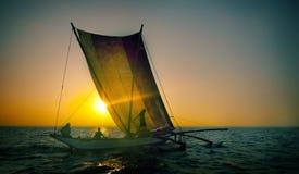 Fiskare på en katamaran på solnedgångbegreppet Arkivbilder