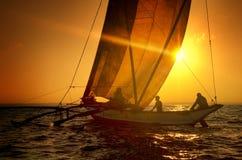 Fiskare på en katamaran på solnedgångbegreppet Arkivbild