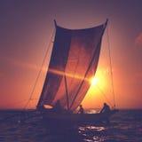 Fiskare på en katamaran på solnedgången Arkivfoton