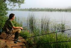Fiskare på en kust av floden Royaltyfri Bild
