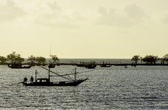 Fiskare på fartyget och fiskebåtarna som parkeras på havskustlinjen på Laem den thian stranden, Chumphon i Thailand royaltyfri fotografi