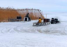 Fiskare på isen som är klar att gå i den elektriska släden som är ytterligare från kusten, snövesslor för vinterfiske arkivfoto