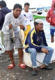 Fiskare på Makassars marknaden för den Paotere fisken visar av något av Royaltyfri Bild