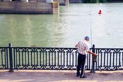 Fiskare på pir med en metspö Pir med räcke vid floden Metallräcke på pir Fiskare under bron royaltyfria foton
