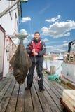 Fiskare på pir med en stor fisk hälleflundra Royaltyfria Bilder