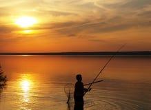 Fiskare på sjön på solnedgången Royaltyfri Bild