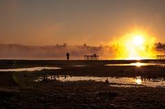 Fiskare på soluppgångbakgrund arkivbilder