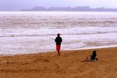 Fiskare på stranden Arkivbild