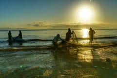 Fiskare som drar fisknätet arkivbild