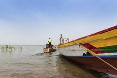 Fiskare som förbereder deras kanoter i porten av staden av Cacheu, i Guinea Bissau arkivfoto