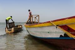 Fiskare som förbereder deras kanoter i porten av staden av Cacheu, i Guinea Bissau royaltyfria foton