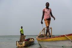 Fiskare som förbereder deras kanoter i porten av staden av Cacheu, i Guinea Bissau arkivfoton